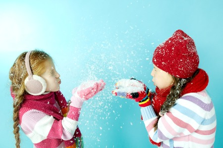 warm clothing: Two little girls in warm clothing blowing snow at each other