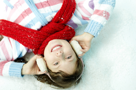 earmuffs: : Portrait of cheerful girl lying on snow in ear muffs and smiling