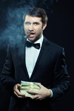 hombre fumando puro: Retrato de hombre presentable fumar cigarro y la celebración de dinero