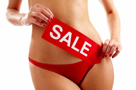 sale tag: Torso of woman in red panties holding SALE tablet