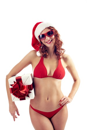 christmas bonus: Portrait of woman in bikini and sunglasses wearing Santa cap and holding gift box