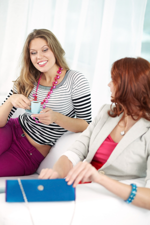 curiously: Young woman looking curiously at what her friend taking out of clutch Stock Photo