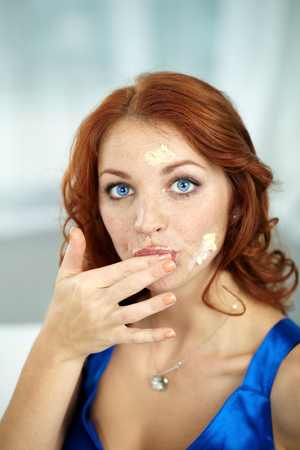 finger licking: Portrait of young woman tasting cream and looking at camera