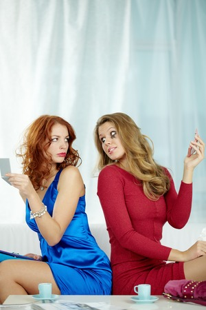Two women with smeared cosmetics sitting on sofa and looking at each other in anger Stock Photo