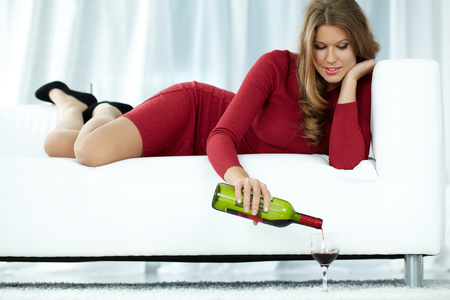 unwind: Young woman lying on sofa and pouring wine into glass