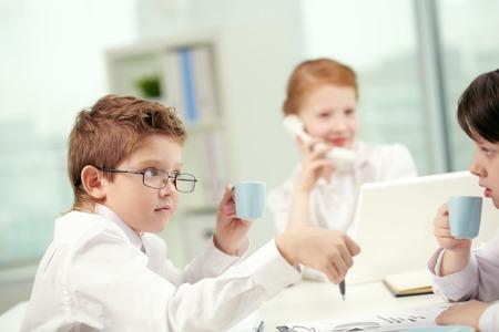 Kleine Kinder trinken Kaffee im Büro und kommunizieren Standard-Bild