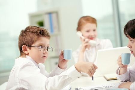 business roles: Little children drinking coffee in office and communicating