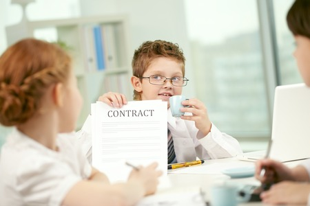 business roles: Little businessman showing contract to his colleagues Stock Photo