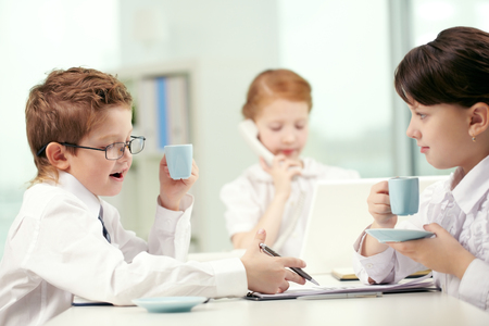 business roles: Businesspeople-like children drinking coffee and discussing documents in office