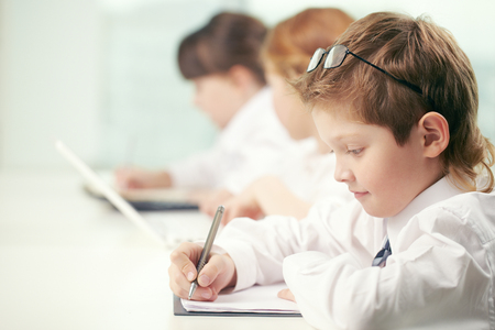 classwork: Little boy making classwork with other pupils