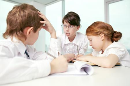 debating: Three little children debating in classroom Stock Photo