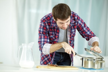 inexperienced: Portrait of man preparing food at kitchen