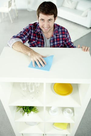 dutiful: Man cleaning shelves whatnot in his house, looking at camera and smiling