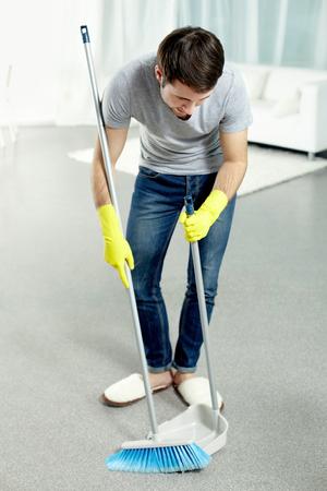 dutiful: Young man washing floor at home