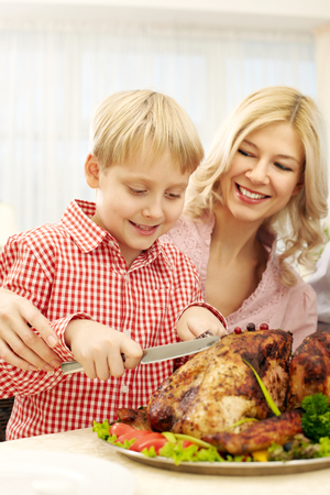 Little boy cutting turkey together with his mother at Thanksgiving Day