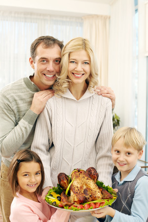 Portrait of happy family of four looking at camera and holding roast turkey Stock Photo