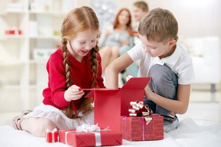 christmas gifts: Little boy taking something out of gift box together with his sister Stock Photo