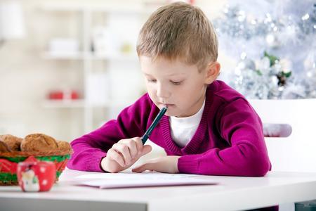 Portret van weinig jongen schrijven aan de Kerstman op kerstavond Stockfoto