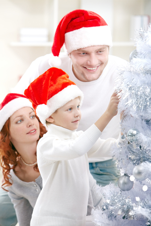 christmas spirit: Little boy decorating Christmas tree together with his parents