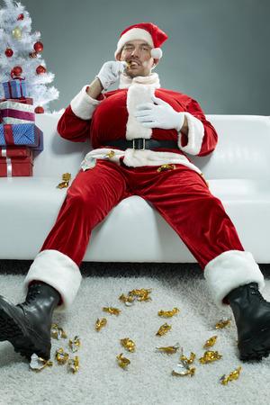 Portrait of evil Santa devouring chocolate candies