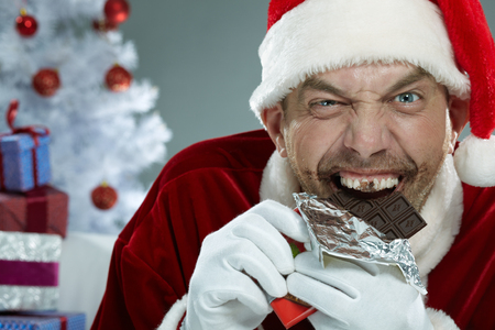 devouring: Wicked Santa Claus devouring chocolate and looking at camera