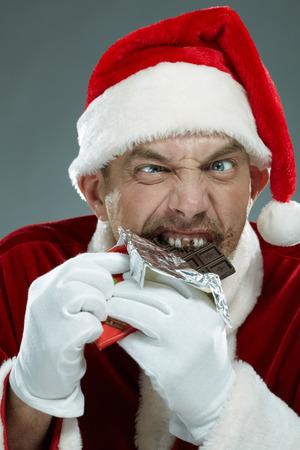malicious: Portrait of malicious Santa Claus chewing chocolate Stock Photo
