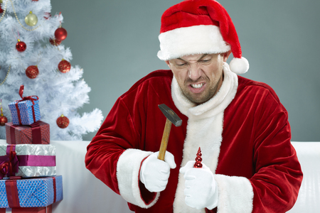 Wicked Santa breaking Christmas decorations with a hammer Banco de Imagens