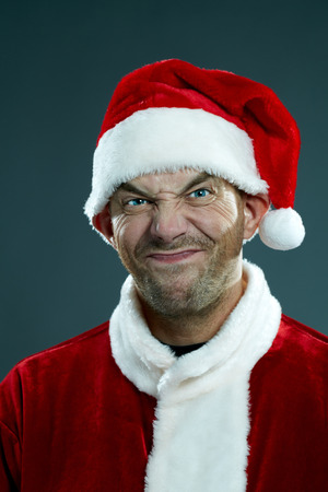disapproving: Portrait of man in costume of Santa Claus looking at camera and making a face