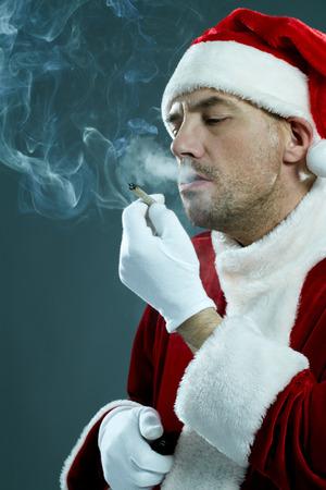 persona fumando: Retrato de la inhalación de hombre en el traje de Santa