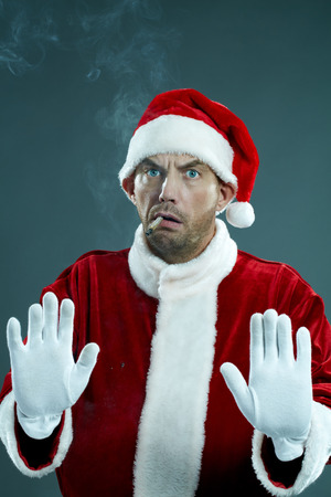 Portrait of displeased man in Santa clothing with cigarette