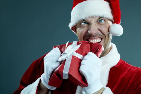 Aggressive Santa Claus biting a gift box