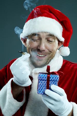 Santa Claus smoking narcotic cigarette and sneering at a gift box