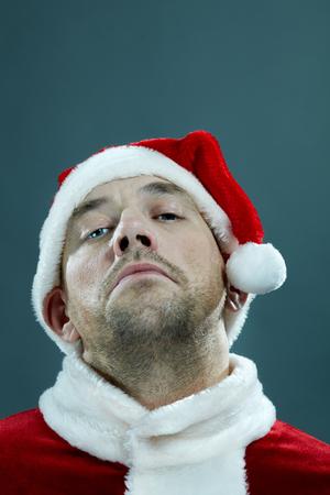 Portrait of man in Santa costume looking at camera arrogantly