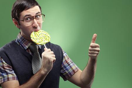 Nerd boy sucking a lollipop and showing big thumb