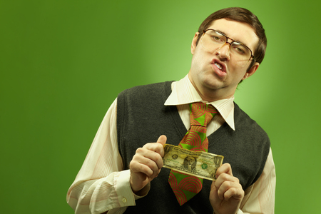 aggravated: Portrait of an arrogant nerd showing a crumpled dollar banknote Stock Photo