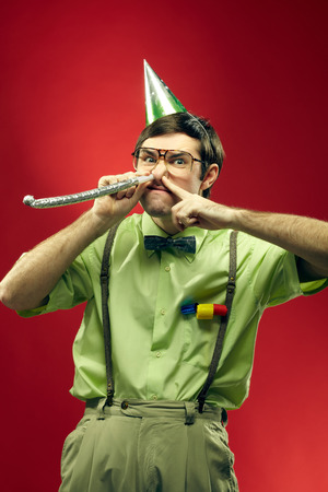 Portrait of nerd in party hat blowing his nose into party horn
