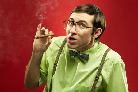 Suspicious nerd smoking a cigar and looking at camera