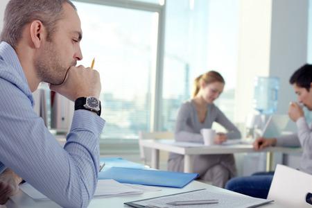 personas pensando: Hombre pensativo que trabaja en la oficina con otras personas de la Oficina