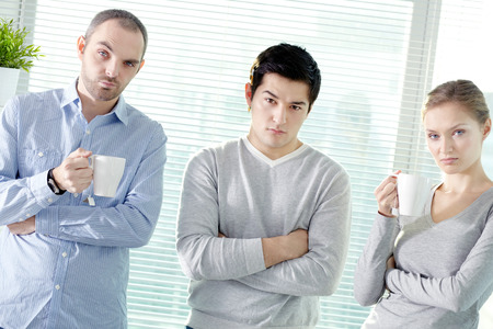intimidating: Portrait of young business team looking seriously at camera