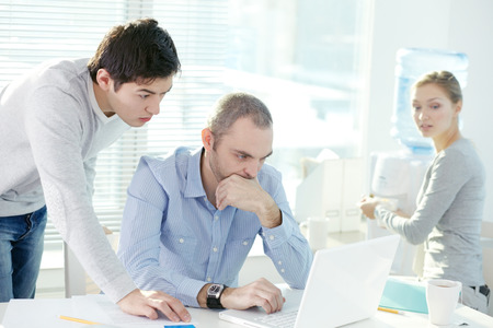 puzzling: Two businessmen corresponding with their colleagues through internet and receiving puzzling e-mail Stock Photo