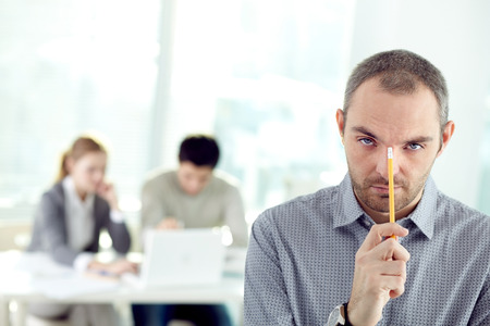 everyday jobs: Serious businessman looking at camera with pensive expression