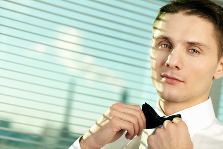 tied knot: Young businessman adjusting tied knot while posing in the background of his factory