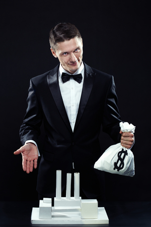 artificial model: Businessman with money sack standing at artificial model of old-fashioned factory