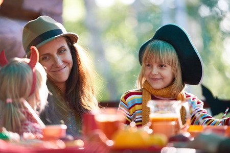 Young woman and her daughter looking at little girl at dinner Stock Photo