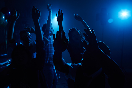ecstatic: Group of ecstatic people dancing in night club