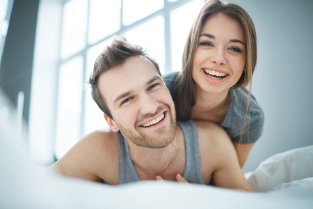 men and women: Cheerful couple lying in bed in the morning