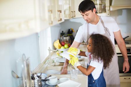 lavar trastes: Los pequeños platos de lavado de niña con su padre cerca Foto de archivo