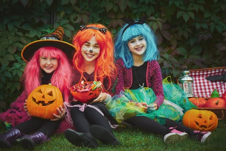 repent: Three witches in wigs sitting on grass Stock Photo