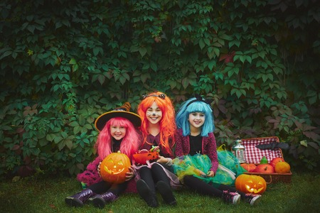 Little girls in Halloween attire looking at camera outdoors
