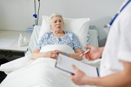elderly adults: Elderly patient listening to her doctor prescriptions while lying in bed Stock Photo